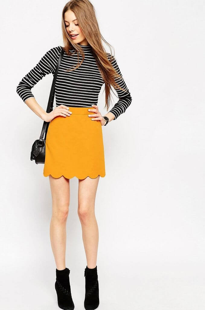 Model seen with a bright yellow scallop skirt, striped top, black boots and a sling bag to match