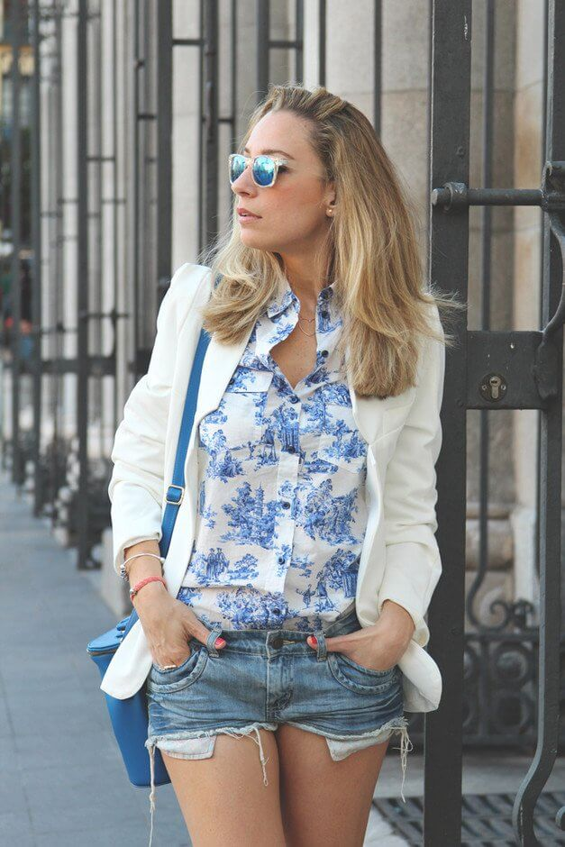Model sports a printed shirt under a white blazer and mini denim shorts, a blue sling bag and Ray Bans to complete the outfit