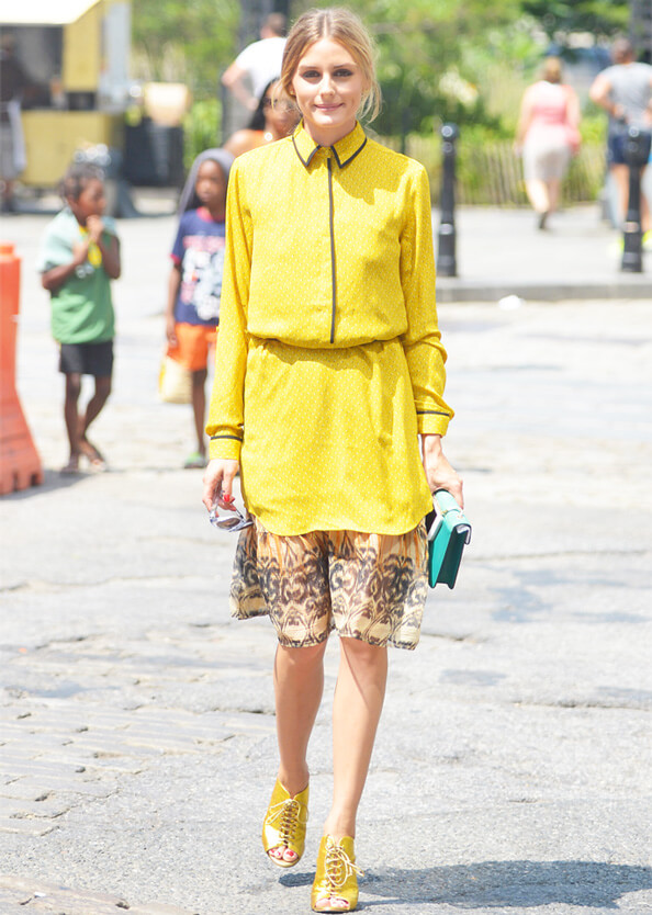 Model poses with a yellow long-sleeved collared top, a flowy skirt, yellow sandals and a cute purse to accessorize