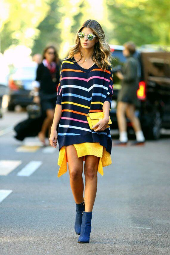 Model is wearing an oversized sweater with colorful stripes, boots to match, a yellow clutch and statement glasses