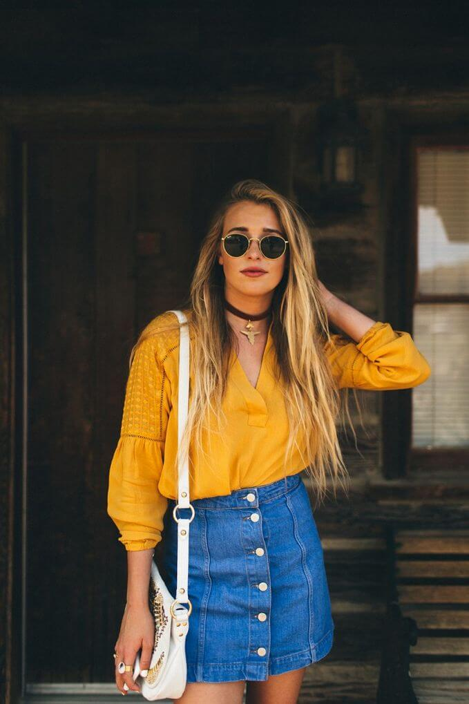 Model poses with a gold top, blue denim skirt, a sling bag, choker and sunglasses to accessorize