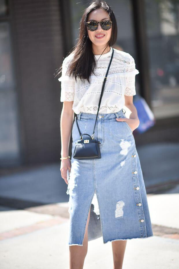 Model wearing a denim skirt with a front split and white shirt, a black sling bag and statement glasses to match
