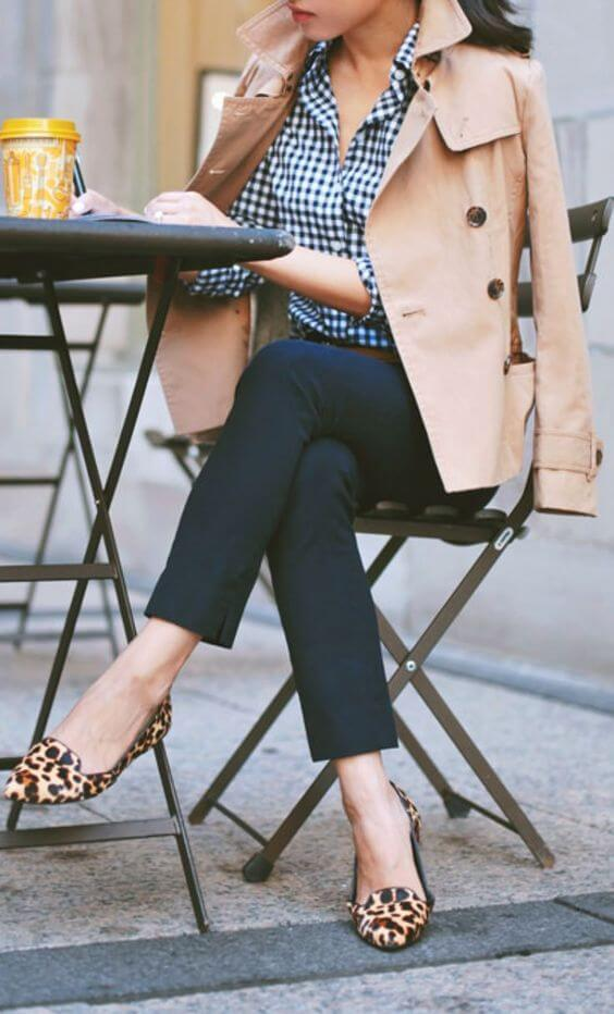Model is seen mix matching a checkered shirt and animal printed flats, a trench coat to finish up the look