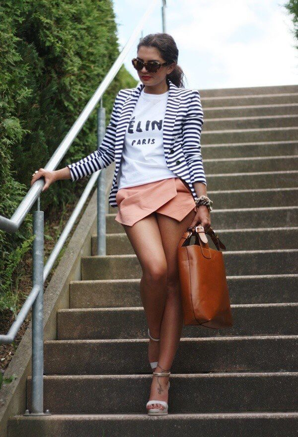 Model accentuates her white t-shirt and striped blazer with pink origami shorts, high heels , a big bag and statement glasses