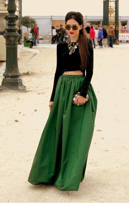Model shines in an emerald maxi skirt with a black long-sleeved crop top and massive accessories to add drama