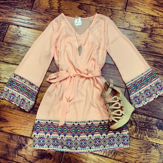 A silky mini dress with ethnic motives paired with wedge shoes and a delicate necklace