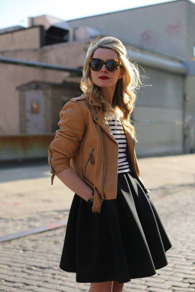 Model with a black flared mini skirt, striped top and leather jacket, statement glasses to match