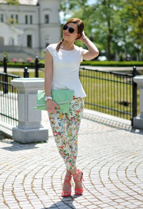 Model poses with a white blouse, floral pants, neon heels and a neutral clutch bag