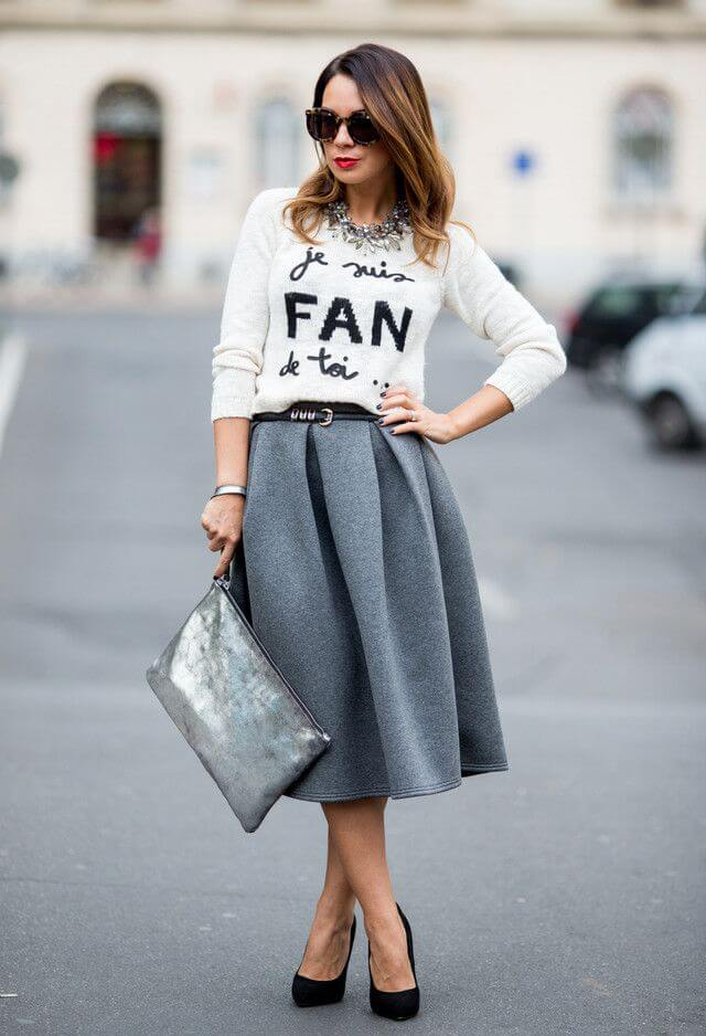 Model graces the street in a knitted sweater, woolen midi skirt, black heels and a big bag with statement glasses