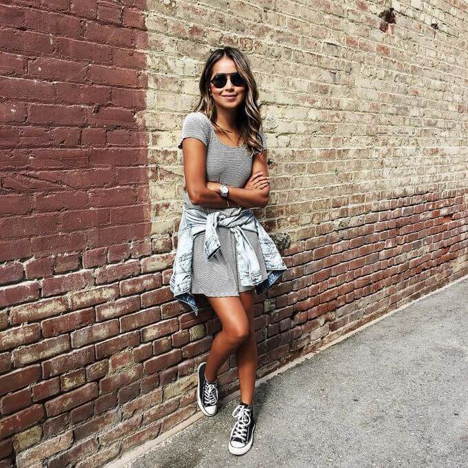 Model poses with a striped gray dress and a denim jacket tied on her waist, converse shoes complete the look