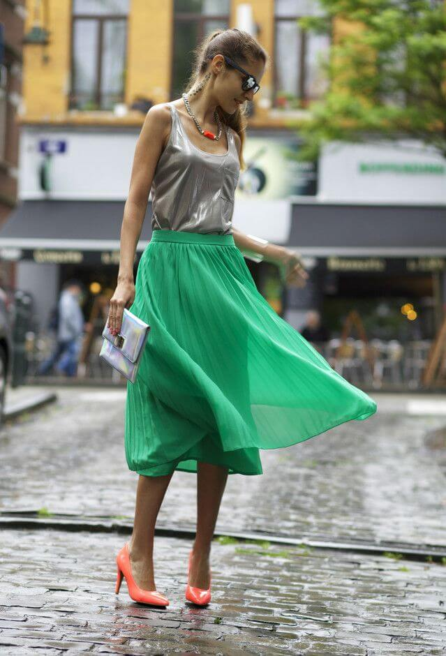 Model is seen with a green metallic tank, green midi skirt, neon heels, a metallic clutch and a gold necklace with sunglasses