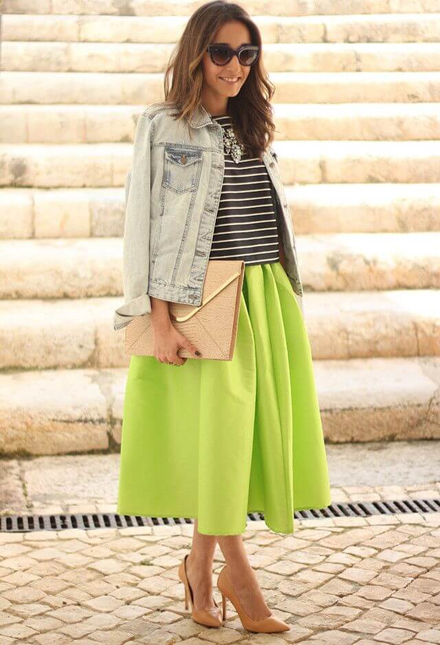 Model in denim jacket, striped top and a green midi skirt and heels