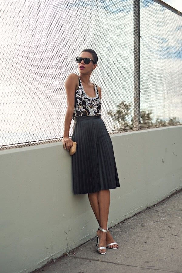 Model is seen in a statement top, high-waisted midi skirt, strap heels and black sunglasses