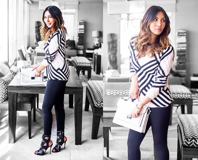 Model poses with her striped shirt and leggings, sexy black heels and white clutch bag