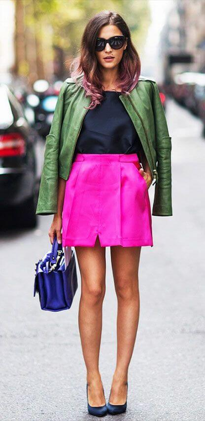 Model poses in a fuchsia skirt, black top, leather jacket on the shoulders and heels to complete the look