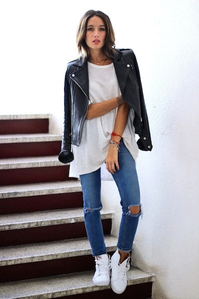 Model with white shirt, leather jacket and ripped jeans