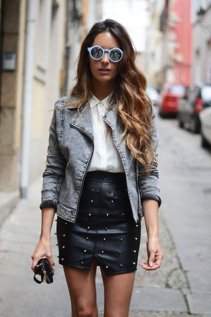 Model is wearing a studded leather skirt, white shirt and denim jacket