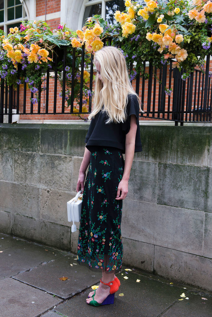 Model creates a vibrant twist with the colorful wedge shoes to complete a simple black shirt and long floral skirt, a bag can be an accessory too