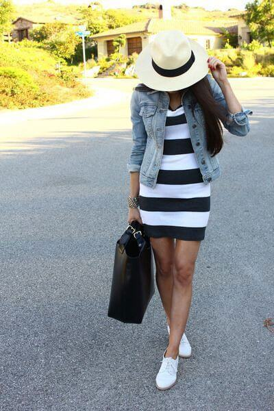 Model poses with her mini black and white dress, white loafers, a denim jacket, hat and an oversized black bag