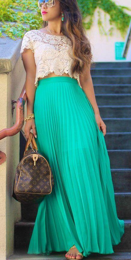 Model holds a Louis Vuitton bag with a mint maxi skirt and a lacy crop top