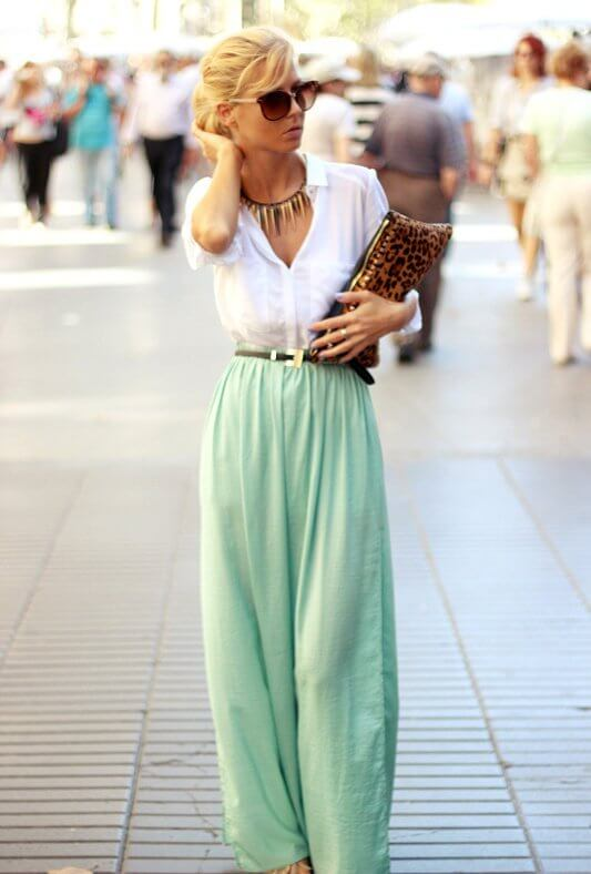 Model poses in a white blouse, mint colored maxi skirt, animal print clutch bag, statement necklace and sunglasses