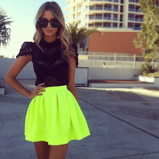 Model poses in neon yellow mini skirt and black lacy top, statement glasses for that edge