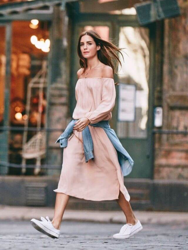 Model walks in a neutral off-shoulder dress and a jacket tied around the waist, converse to give that airy vibe