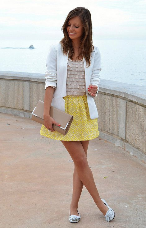 Model combines a geometric yellow skirt with a neutral shirt and blazers, a clutch and stylish ballet flats