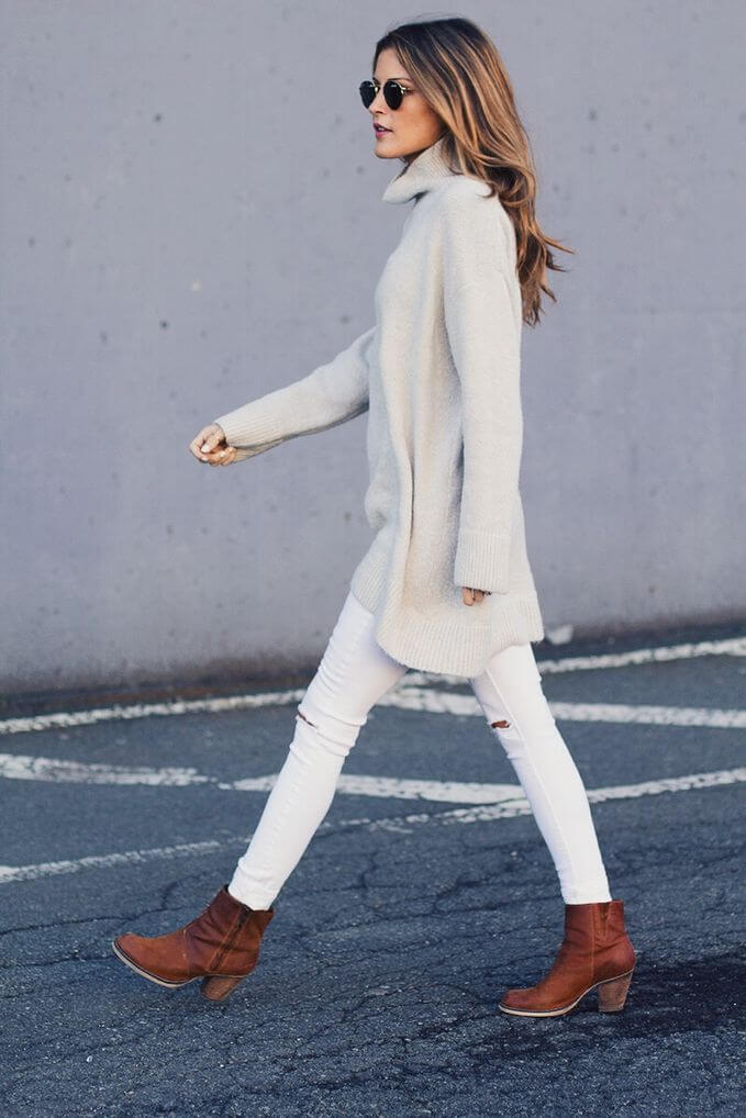 Model walks in an oversized sweater, white jeans and boots