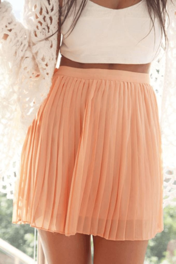 This coral mini skirt is pleated and easy to combine with basic shirts