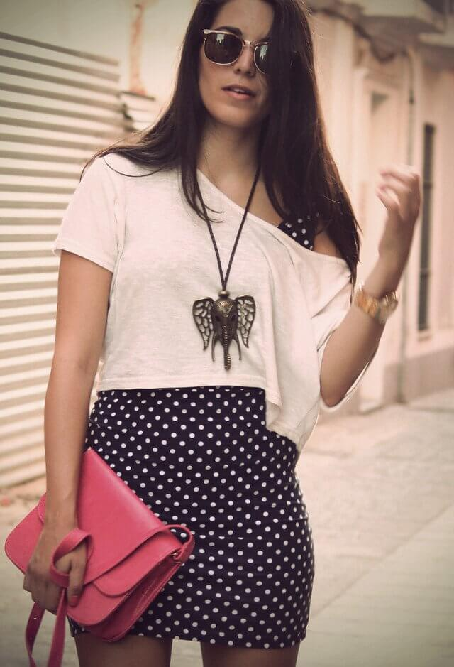 Model combines a polka dress and a white crop top over it with an elephant statement necklace and a bright pink bag