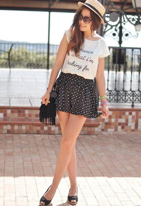 Model is wearing a polka mini skirt, white shirt with a straw hat, peep toe heels and a fringed black bag