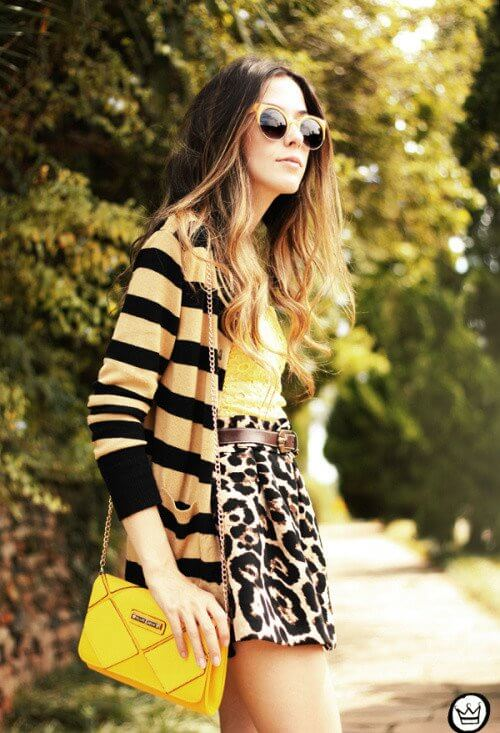 Model is sporting a geometric cardigan and an animal printed skirt of the same color palette, a yellow bag to accentuate