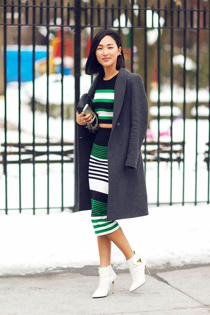 Model is wearing a rainbow striped dress with a long cardigan and white booties and a clutch purse