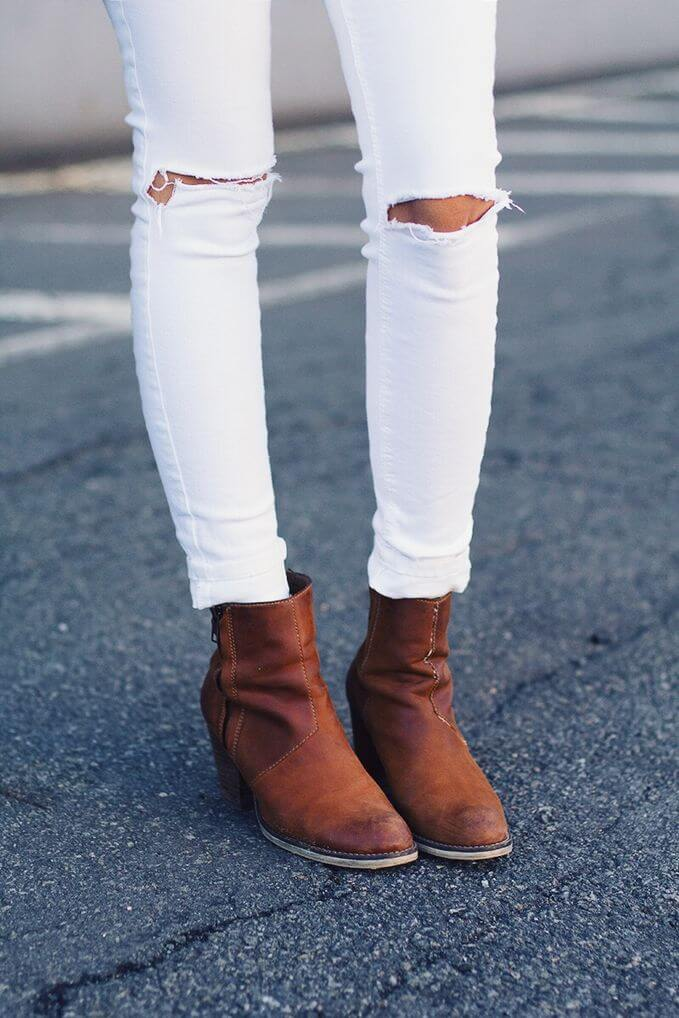Ripped white jeans at the knees and boots