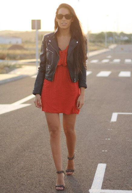 Model walks the streets in a red dress, leather jacket and chained high heels, statement glasses to add more fierceness