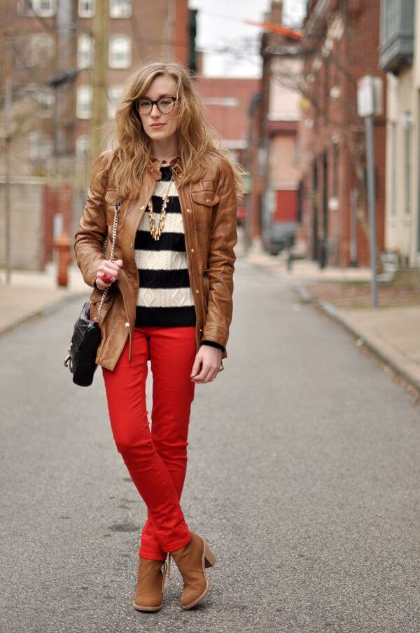 Model seen in a simple striped sweater with a leather jacket, red pants and boots, a sling bag and a long gold necklace to accessorize
