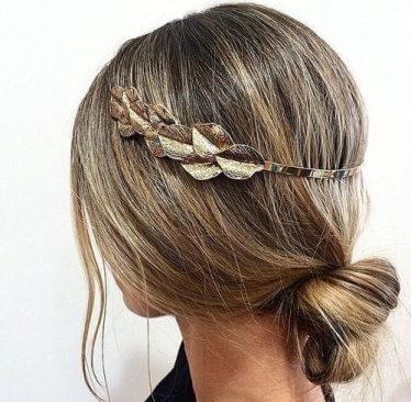 Hair is loosely made into a bun with hair strands in the front, paired with a little hair band