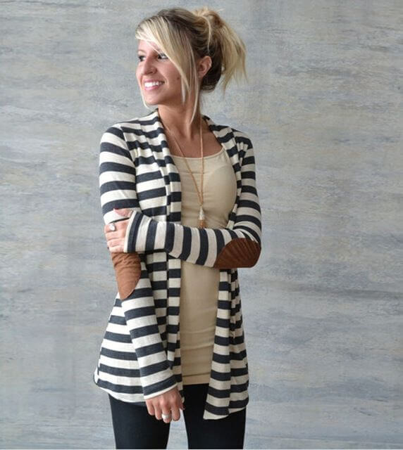 Model looks classy in a striped cardigan with brown elbow patches, a bright top and leggings, a statement necklace to complete