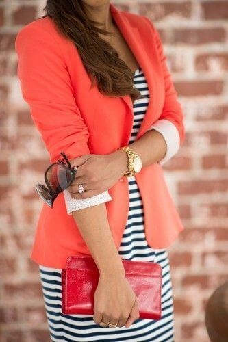 Model showcases her striped dress under an orange blazer, a clutch purse, gold watch and statement glasses