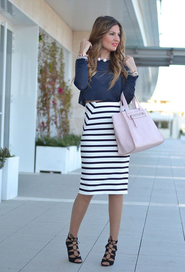 Model is wearing a blue transparent crop top, a high-waisted midi skirt in stripes, black high heels and a big hand bag, accessories highlight the look