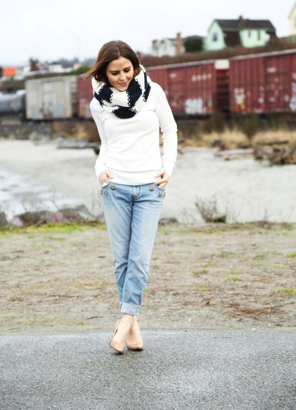 Model looks cozy in a white sweater and denim pants, nude heels and a black and white scarf