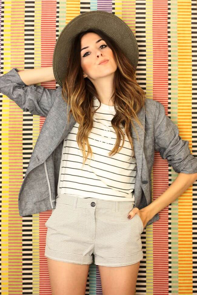 Model is wearing a white shirt with black stripes tucked in striped shorts and a gray blazer, topped off with a big hat for style
