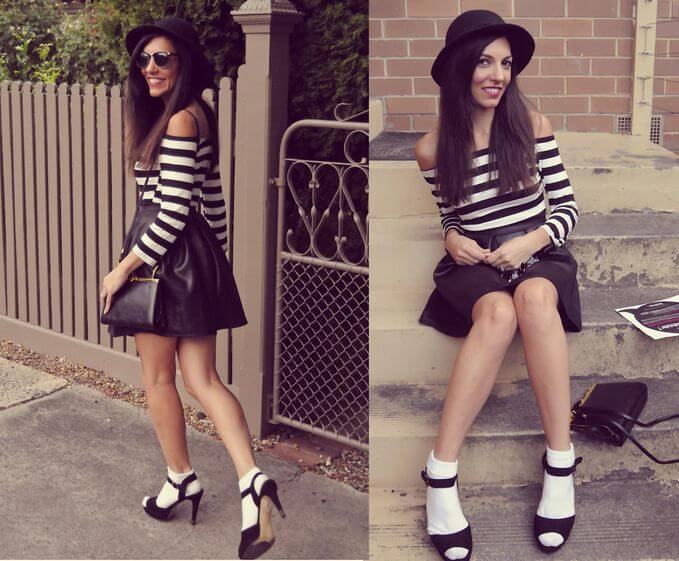 Model is wearing a striped off-shoulder top, black skater skirt, socks and heels, and a sling and hat to match