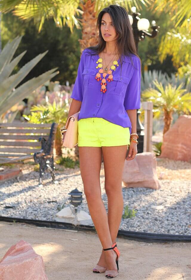 Model poses with a blue shirt and neon yellow shorts, colorful heels, a bright statement necklace, bangles and a clutch bag