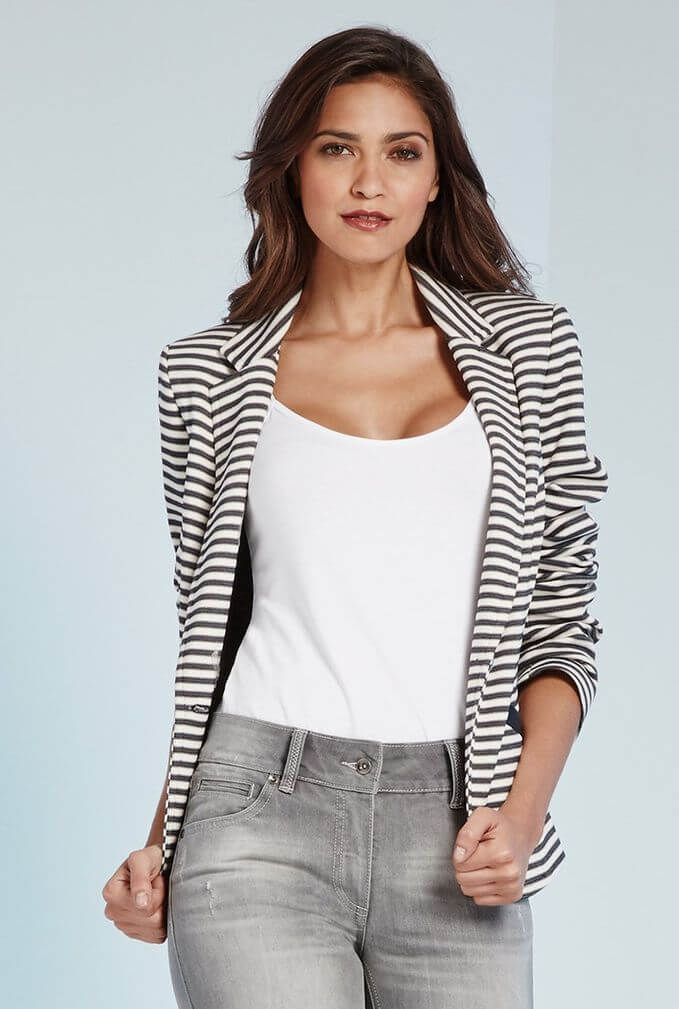 Model is wearing a plain tank tucked in jeans and a striped jacket