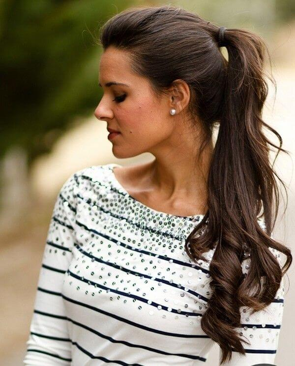 Model sports a ponytail with curls at the end