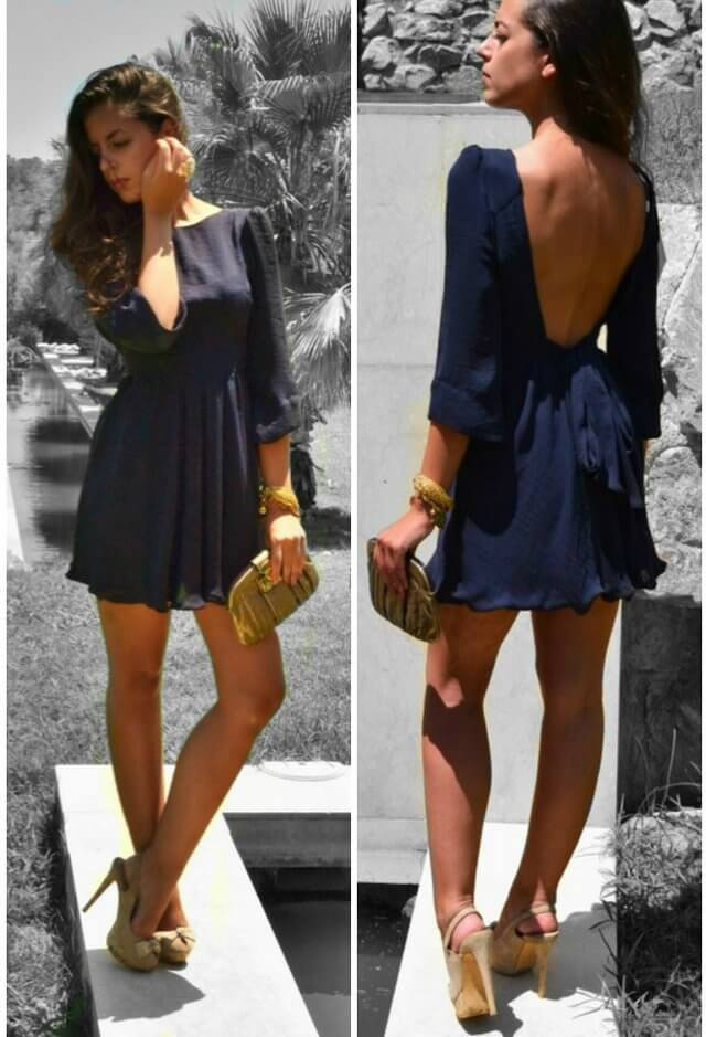 Model slays in a backless mini deep blue dress, brown high heels and a gold bracelet with a clutch purse to match