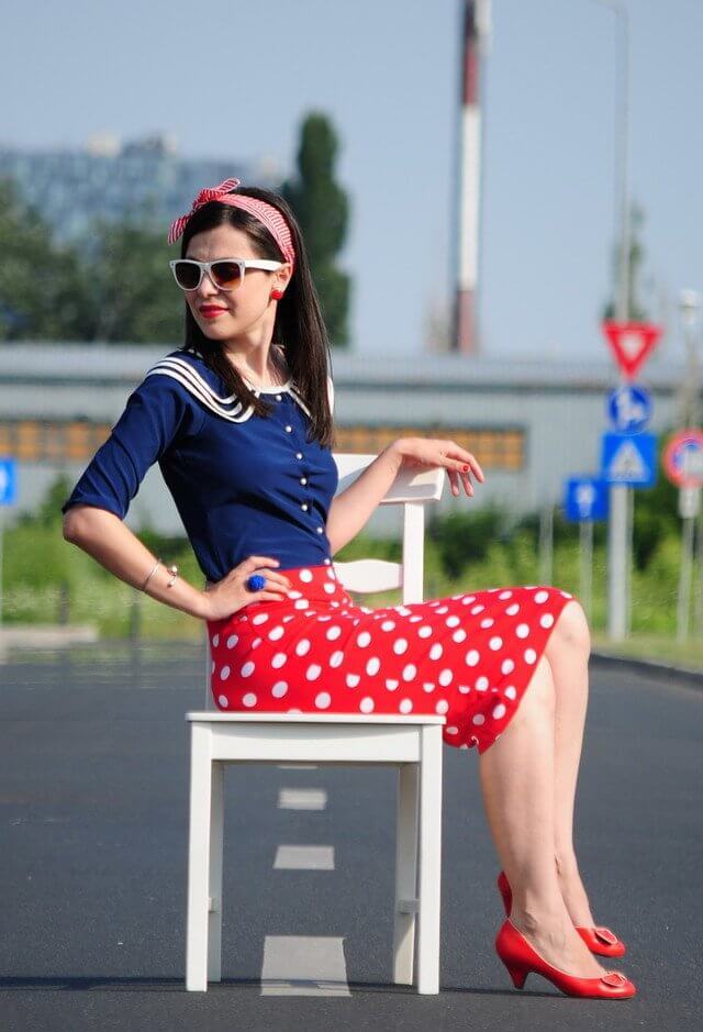 Model sits on a chair in a red polka skirt with matching red heels and a hair tie, blue blouse and a matching ring to balance