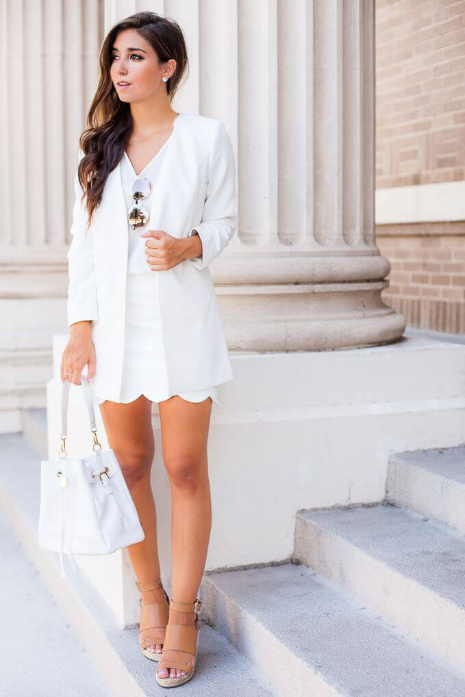 Model in a white dress with white blazers, nude sandals and a white bag
